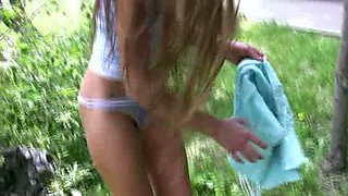 Skinny amateur Russian chick behind the car pisses in her pants