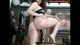 Oiled brunette rides a monster black dildo