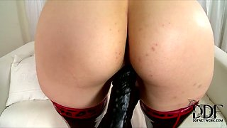 Latex covered domina masturbates in missionary pose with legs spread wide