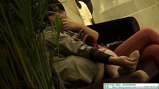 Pantyhosed Asian girl caresses her feet in a public place