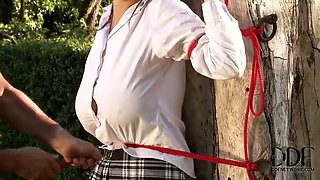 Busty college girl is tied up to the tree in dirty porn video