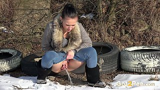 Lovely brunette sexy girl in bllue jeans pisses behind the tires