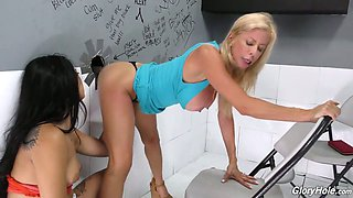 Brunette Gina Valentina and her blond girlfriend go wild in glory hole room