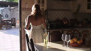 Smiling mature blonde housewife Eve strips in the kitchen