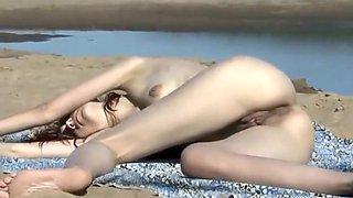 Drunk nude girl lying down on a beach