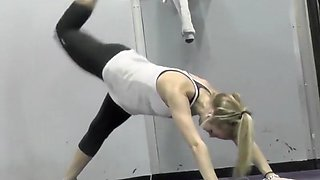 Flexible blonde stretches in the gym